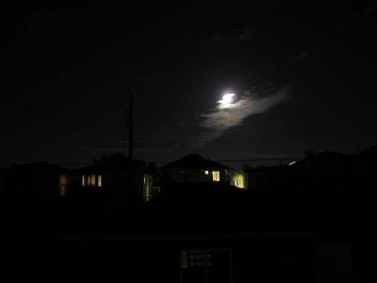 A picture of a UFO shining through the clouds. Or maybe it's the moon, but the moon ain't that bright.